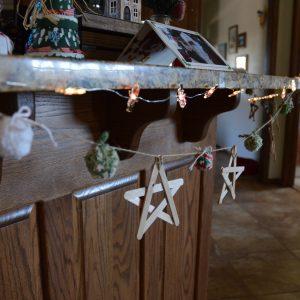 A yarn pom pom garland hanging up for Christmas.